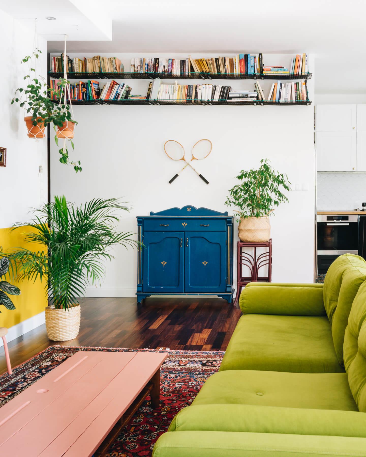 Fragment kolorowego salonu urządzonego w eklektycznym stylu z zieloną kanapą, niebieską szafką, orientalnym dywanem