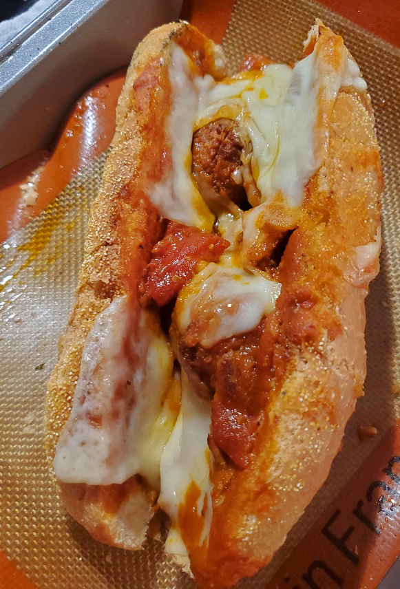 this is a submarine sandwich with a rich tomato sauce, boneless pork spare ribs and Italian sausage smothered in mozzarella