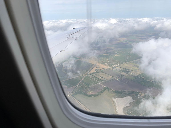 View out the airplane window of fields and wind turbines near Brownsville, TX (Source: Palmia Observatory)