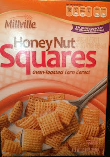 A poorly-cropped image of a Millville Honey Nut Corn Squares Cereal box