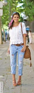 Mulher andando segurando uma bolsa caramelo e usando uma sandália caramelo