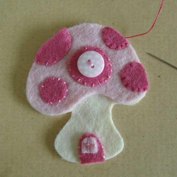 Hand stitching pink spots onto the felt design toadstool