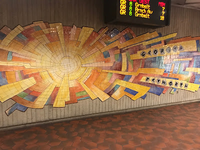 A colorful cracked tile piece of art that looks a little like a sunburst.