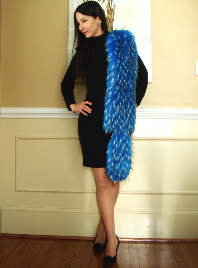 Wearing a black long sleeve dress with blue faux fur stole and black shoes.