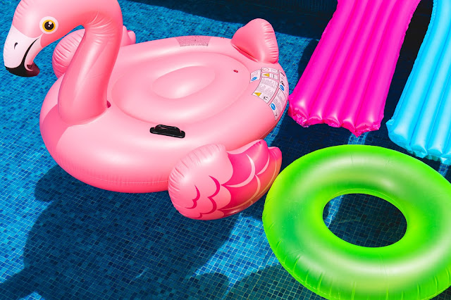 A variety of pool inflatables floating on a pool.