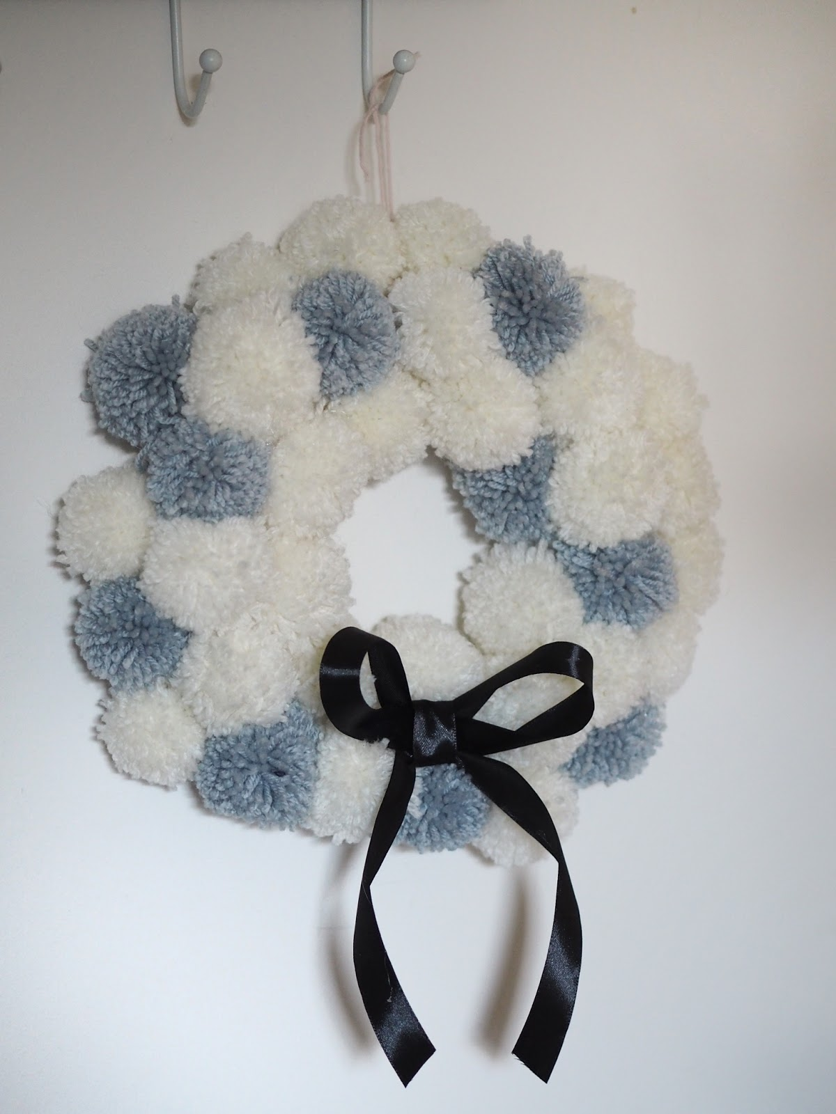 DIY Christmas wreath decor made from wool yarn pom pots and ribbon. Make your own snowball style wreath from woollen pom poms in this simple DIY tutorial budget Christmas decoration.