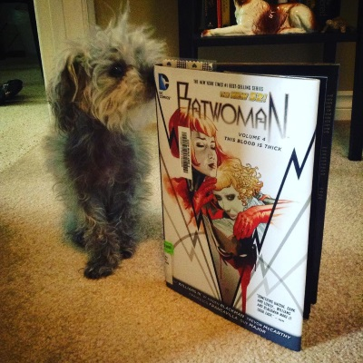 Murchie sniffs an upright, hardcover copy of Batwoman Volume 4. Its white cover features a very pale redhaired woman hugging a very pale blonde woman. Both have bobs and identical features.
