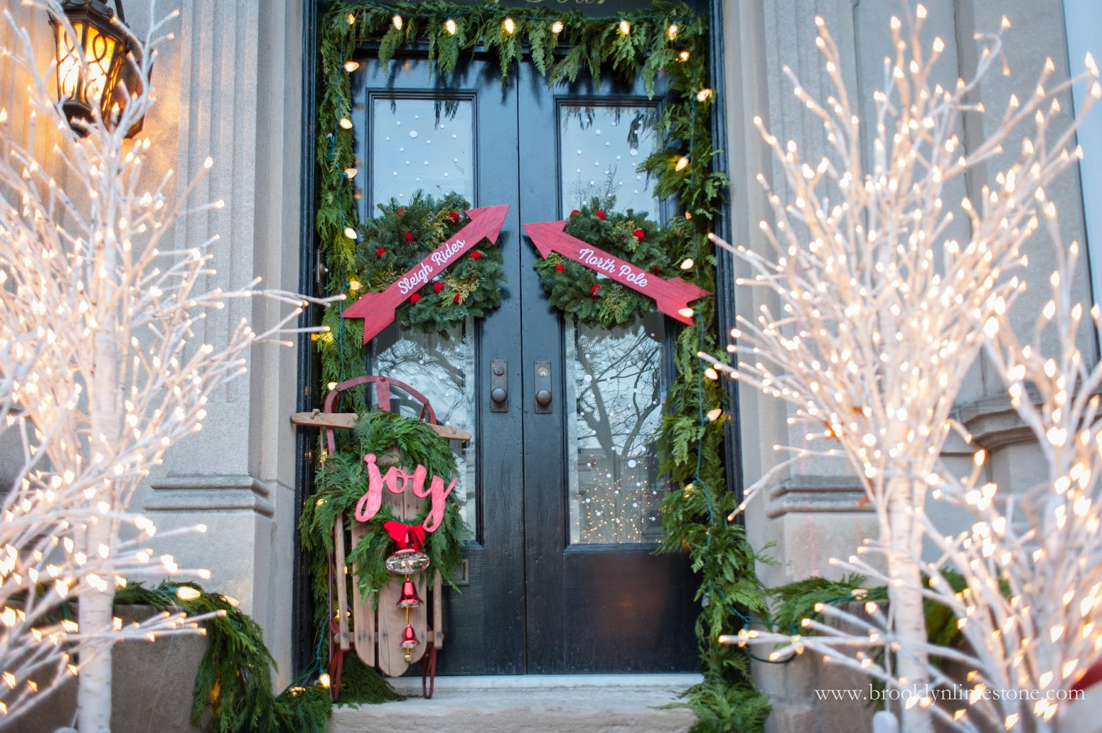 Christmas front door with sleigh and wreaths with arrows