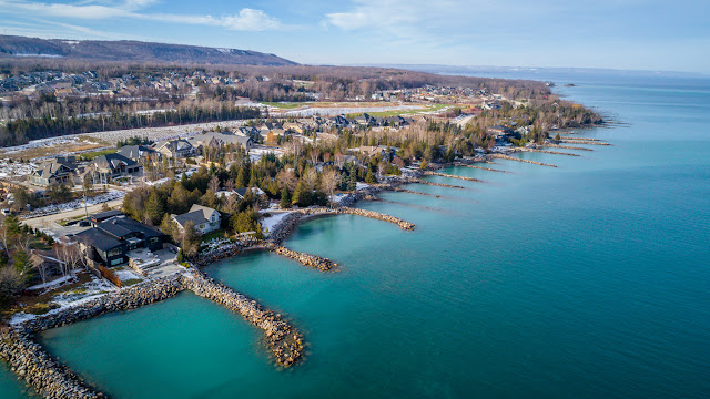 a view from a drone above brilliant blue water on a sunny winter day above Georgian Bay near the shores in Thornbury.