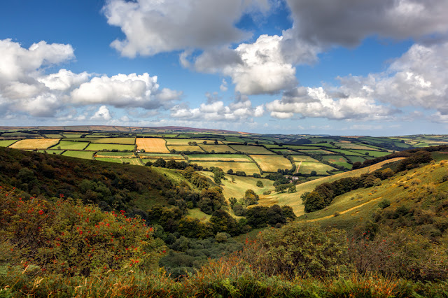 Fluffy clouds drift over patchwork fields in Exmoor's Punchbowl