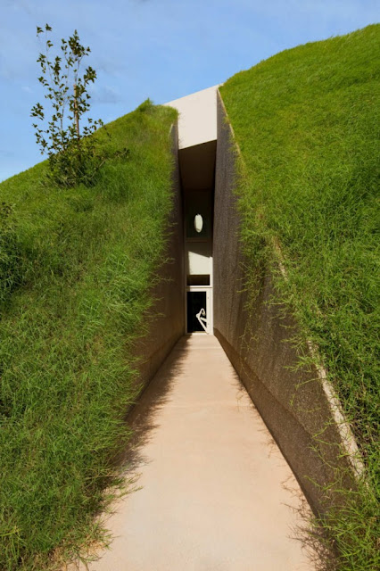 Photo of narrow entrance path surrounded by the grass hill