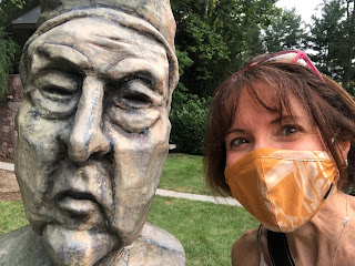 A masked selfie with a stone statue of a stately woman.