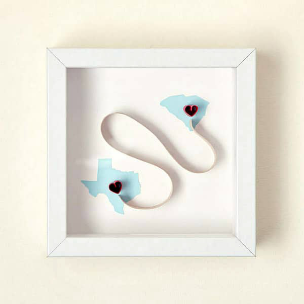 framed shadow box quilled art with gently curved on-edge scroll connecting California and South Carolina, each marked with a red heart