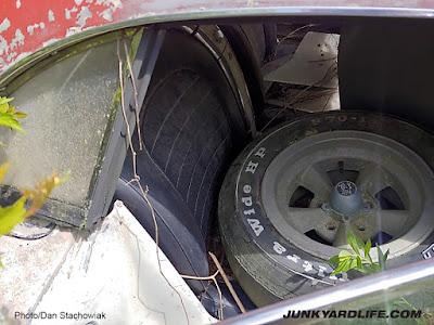 Vintage torque thrust 5-spoke wheel sits on seat inside 1959 Vette.