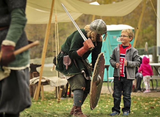 A Viking reenactor chooses a young boy to be his Jarl during Norsk Høstfest Military Appreciation