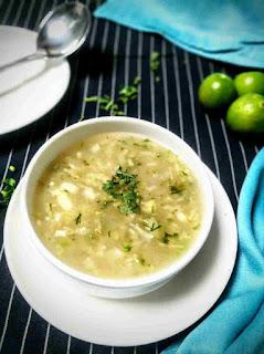 Serving lemon coriander soup in a soup bowl, spoon, whole lemon in background