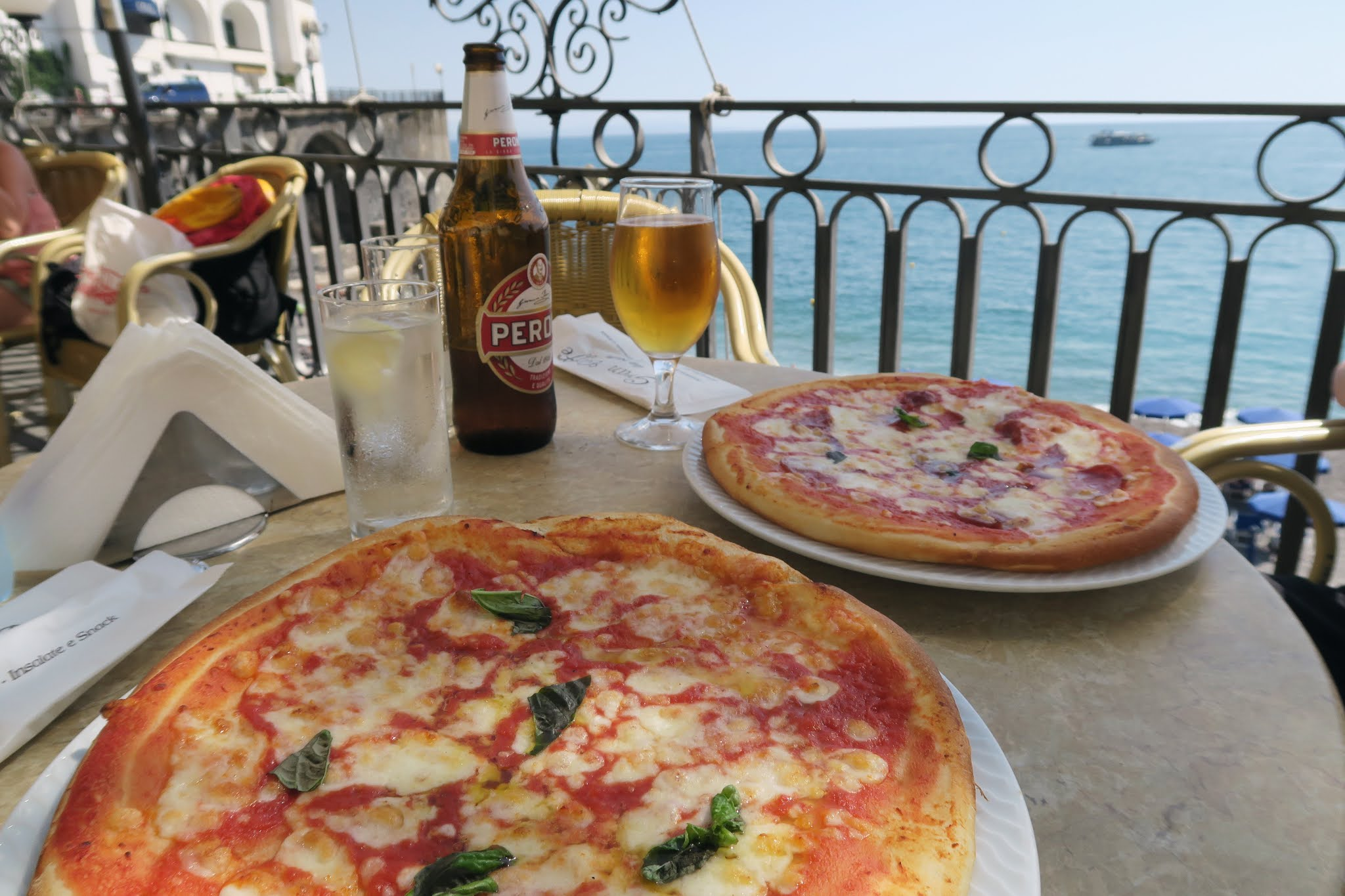 Pizza and beer on a table in front of the blue mediterranean sea.