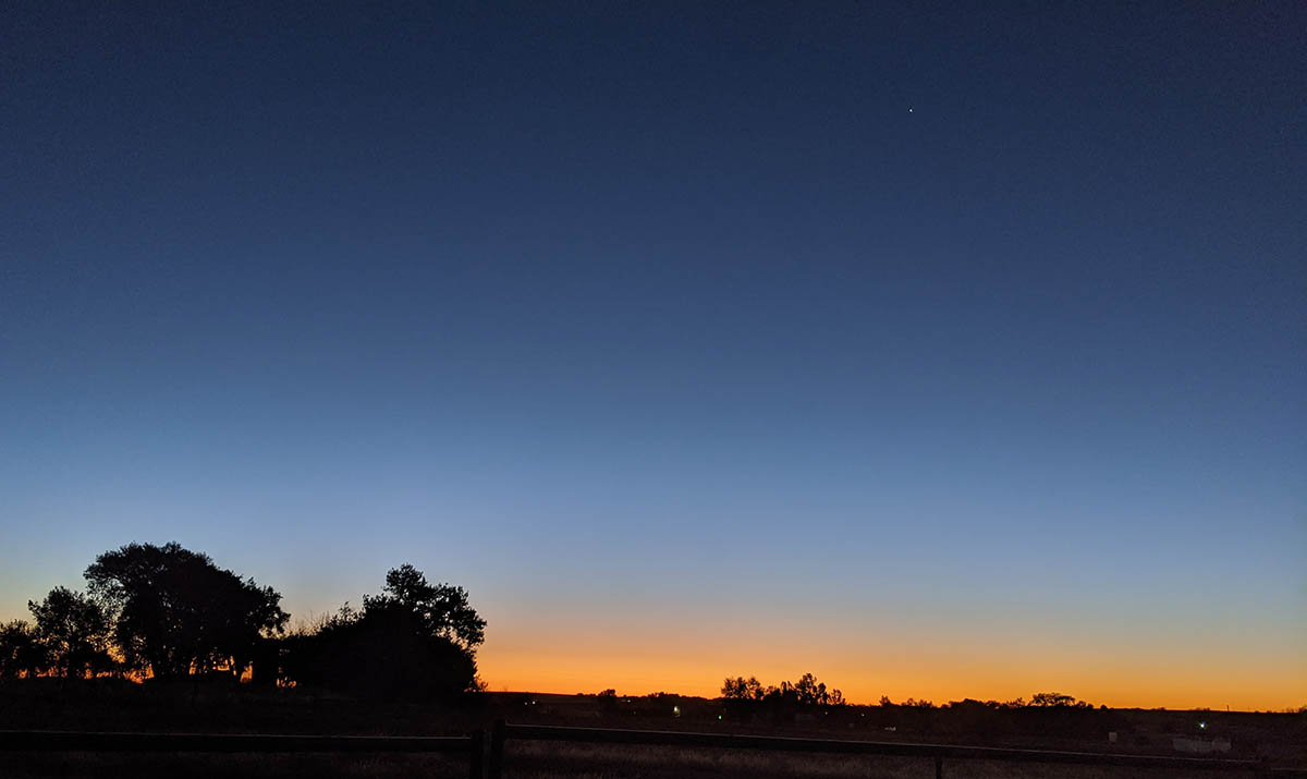 A clear morning sky with Venus on the horizon