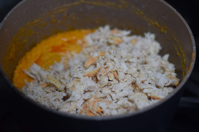 The fully cooked shredded chicken being added to the sauce pan.