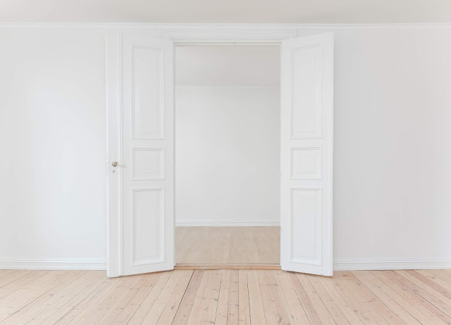 Interior of two double white doors, against white ones with a pale netural floor