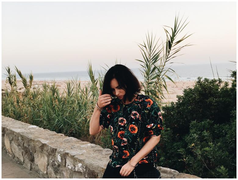 CONIL DE LA FRONTERA - BLACK FLOWER TOP | June Gold wearing a black H&M top with floral print, a black & Other Stories skirt and black & Other Stories shoes