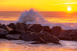 A close-up of a wave crashing into a rock with the sun sitting on the horizon - Ocean Grove, New Jersey