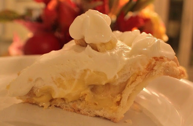 old fashioned homemade banana cream pie in a pie plate with whipped cream on top homemade banana pudding, bananas on top and whipped cream
