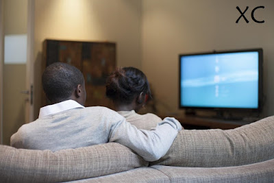 Couple sitting at home and watching TV