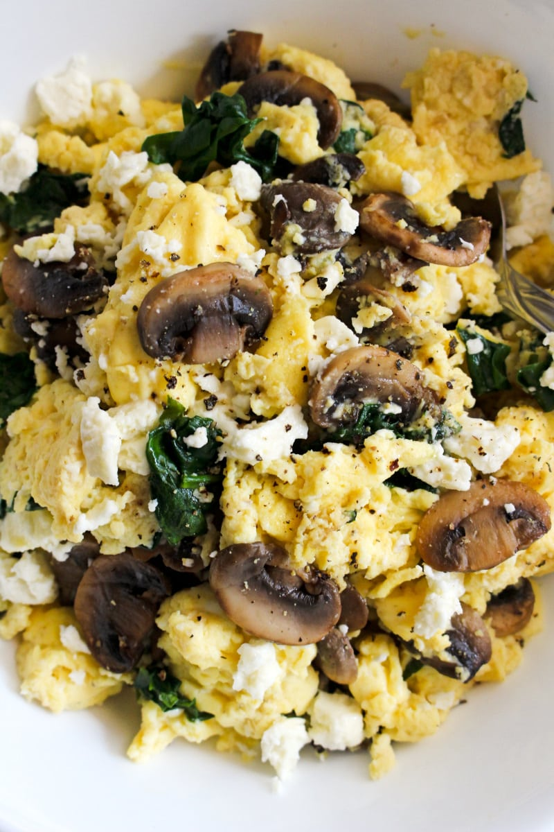 Close up top view of scrambled eggs with mushrooms, feta, and spinach on a white plate.