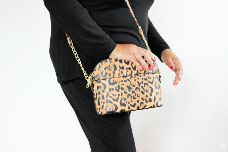 a woman wearing a leopard print purse