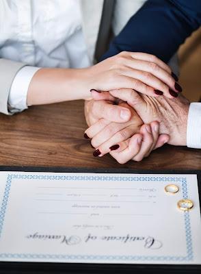 Pareja tomándose de la mano con el certificado de matrimonio y alianzas delante de ellos