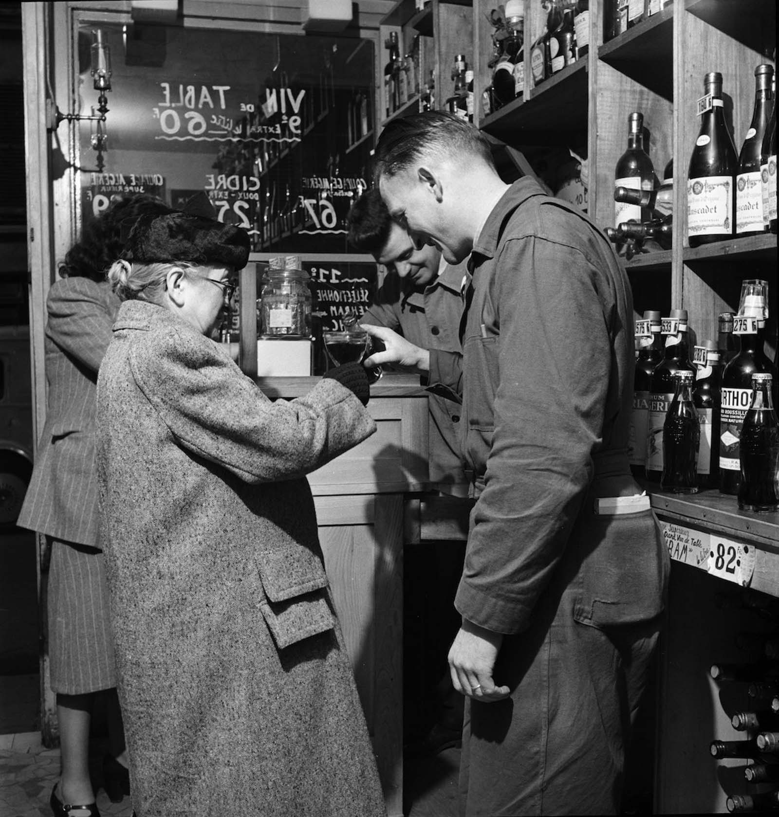 In a Paris shop, a man pours a bottle of Coca-Cola into a glass held by an elderly woman.