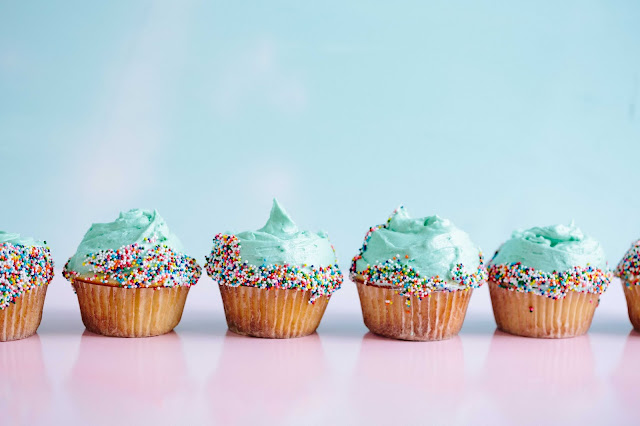 Cupcakes with green frosting & sprinkles lined up:
