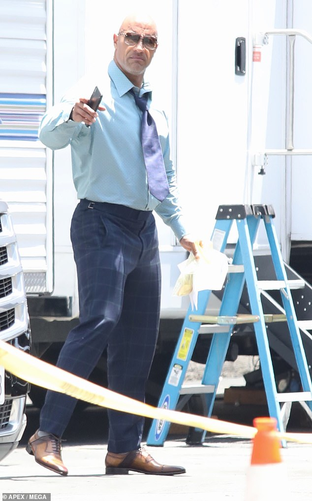 Dwayne 'The Rock' Johnson wears plaid trousers with button up shirt while on the set of Ballers
