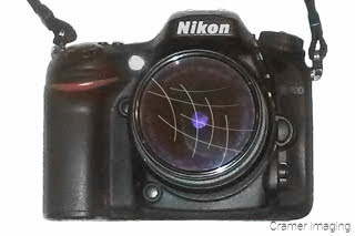 Cramer Imaging's photograph of a DSLR camera with a scratched lens