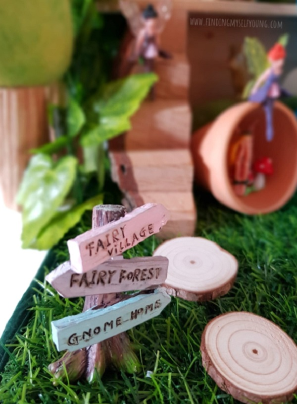 miniature fairy village and forest sign post