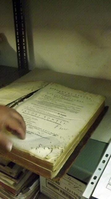 mão manuseando um livro em mau estado