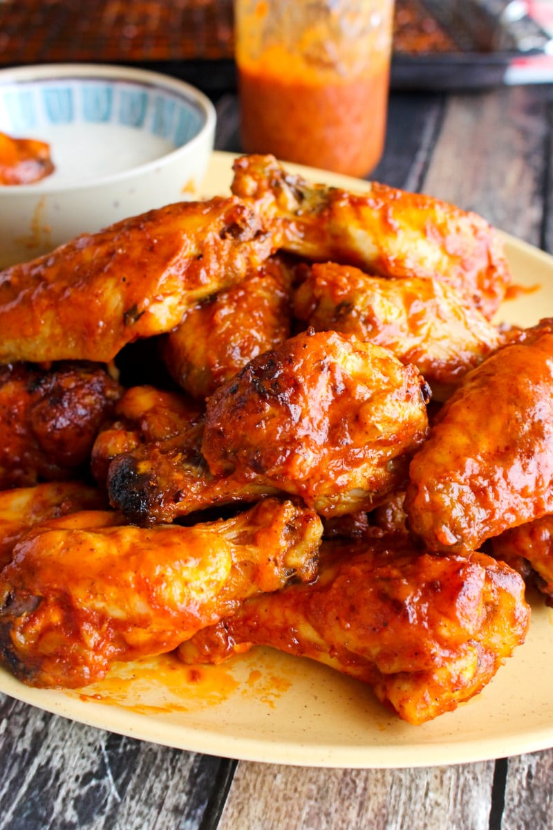 Side view of Baked Buffalo Chicken Wings on a yellow plate on a wood background.