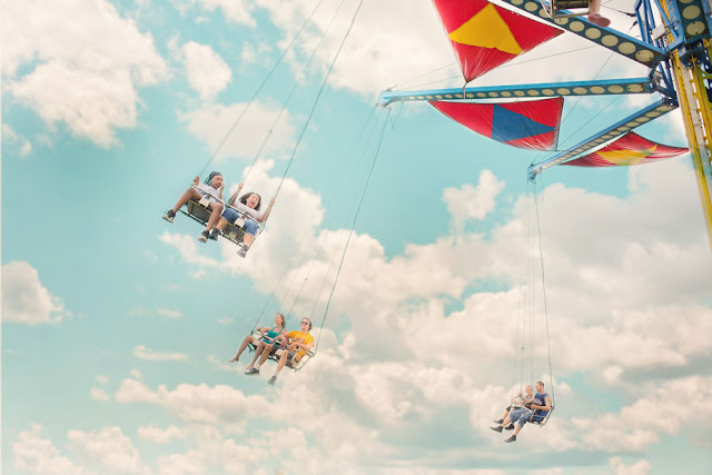 carnival-goers enjoying the swing ride