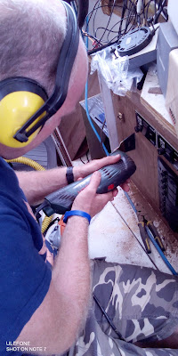man with power tools working on panel