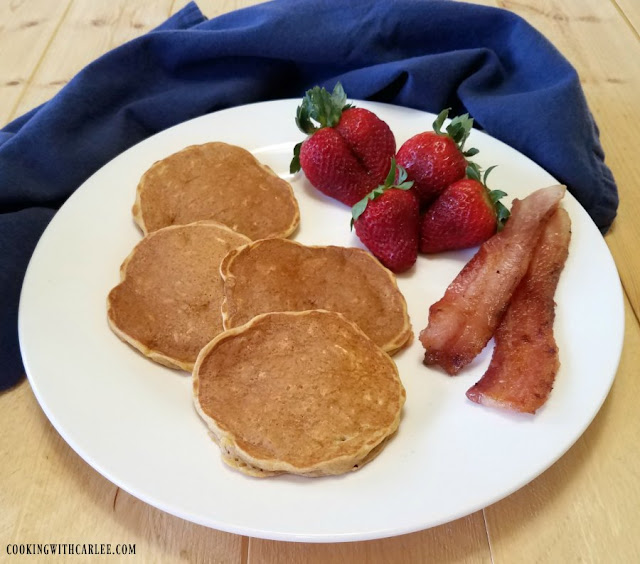 plate of whole grain banana yogurt pancakes with bacon and strawberries