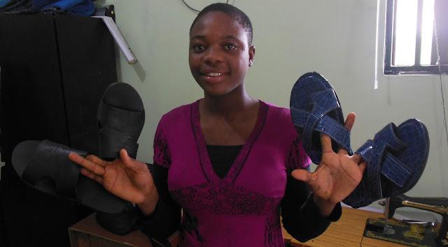 Girl holding Sandals she made
