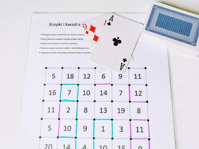 na zdjęciu plansza do gry z zaznaczonymi już odcinkami, obok leży talia kart, wylosowane są karty o wartościach jeden i dziewięć