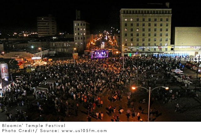a large crowd gathered in the city square for a night festival