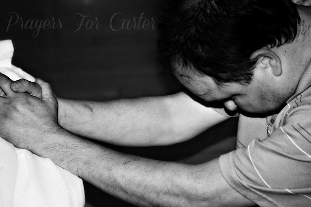 trisomy 13 | man praying at a bedside | rosevinecottagegirls.com
