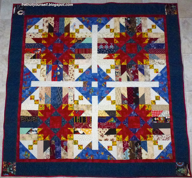 Red, yellow, blue and white fabrics create four large star blocks and a secondary Churn Dash appears when they are set.