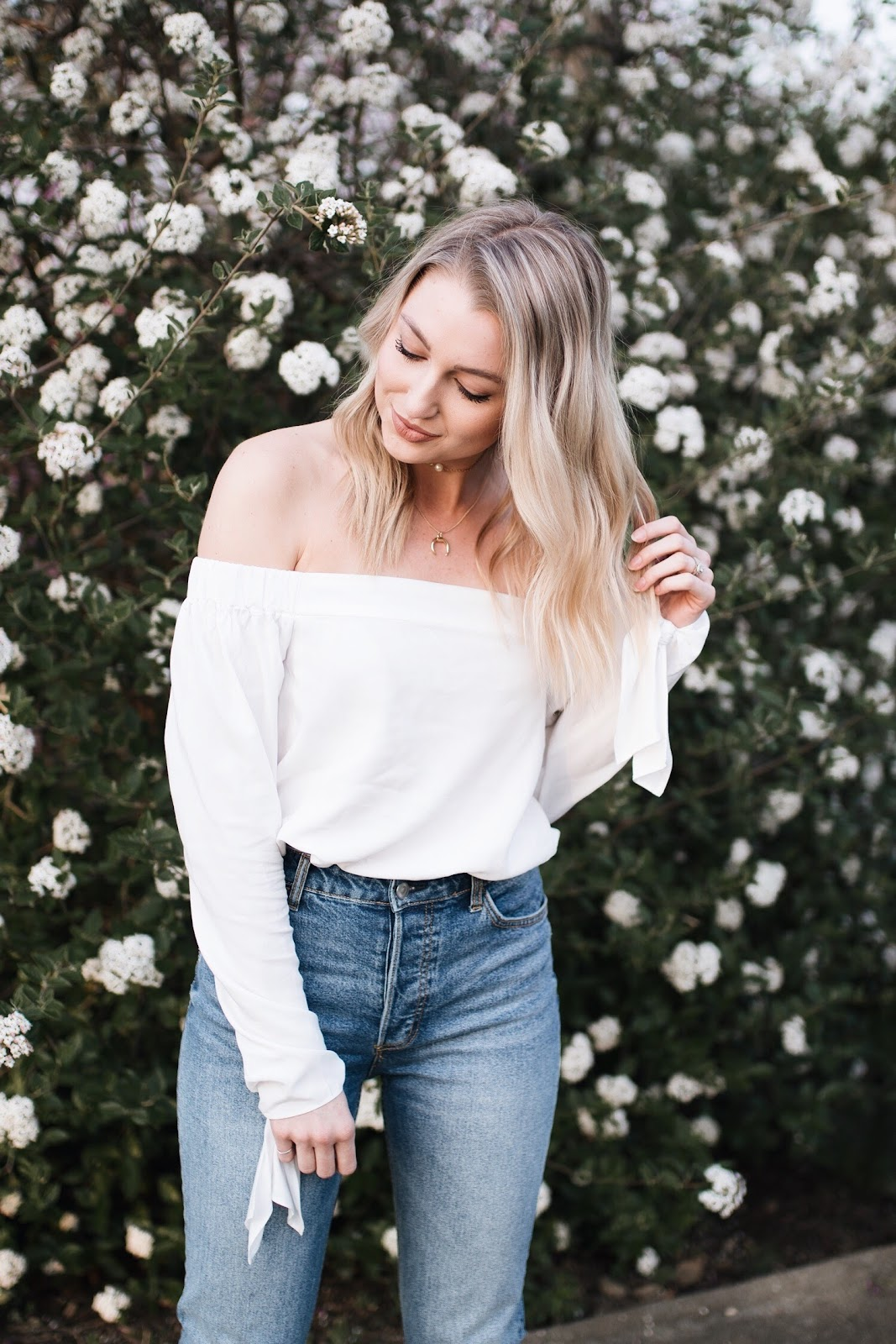 white off-shoulder top tucked into jeans