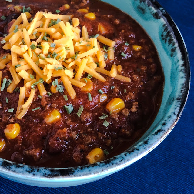 sweet corn & black bean chili in a turquoise bowl with cheese on top