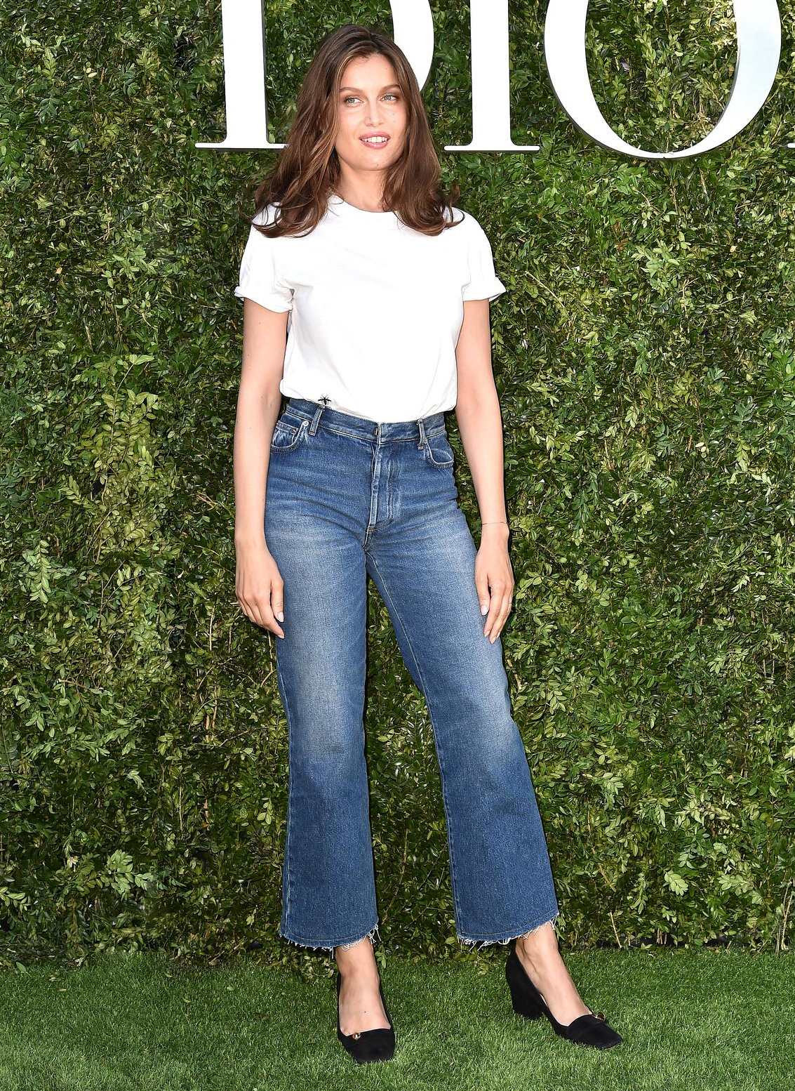 French Girl Style Inspiration — Laetitia Casta Model outfit idea with white t-shirt, flared jeans aand square toe heels