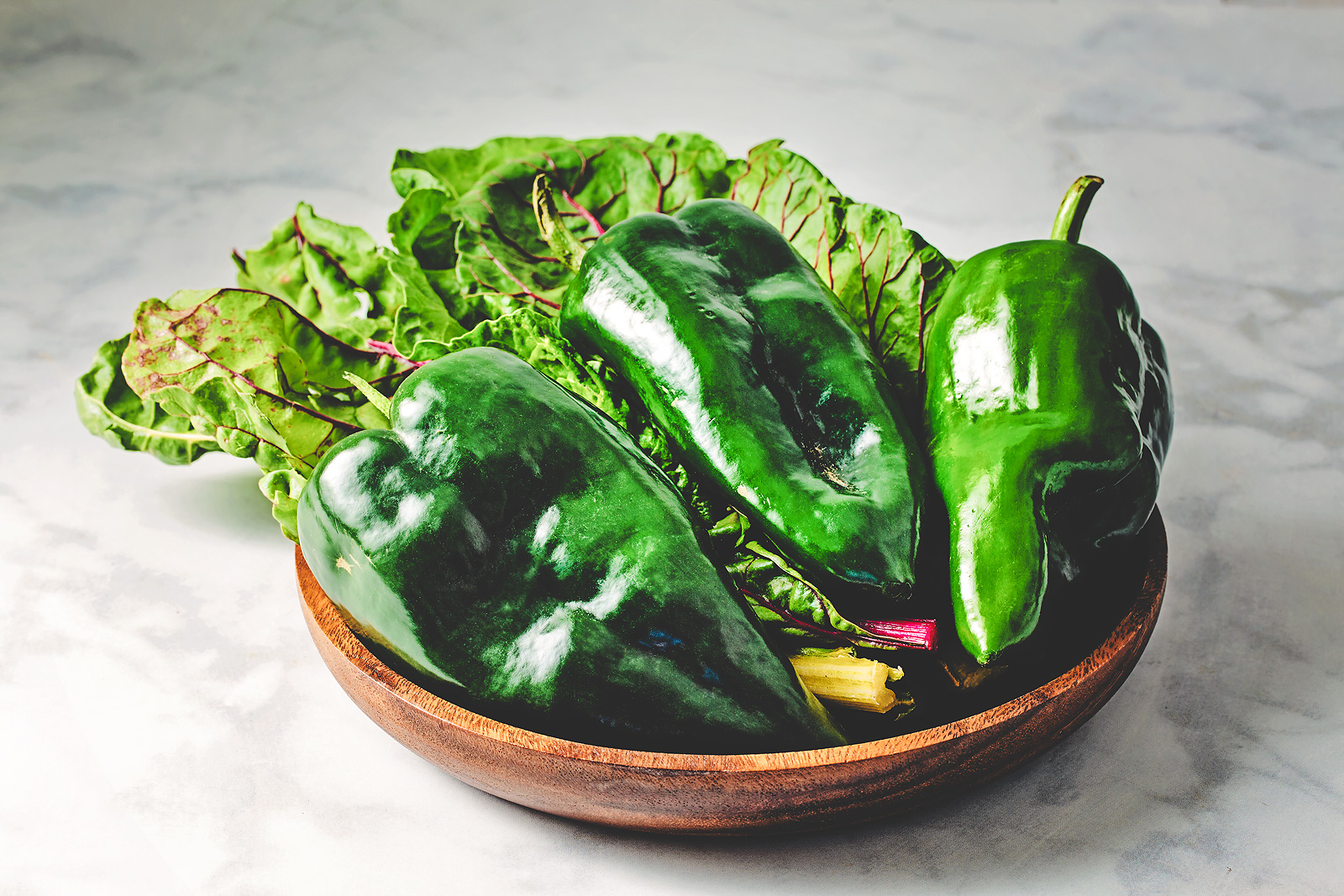 A wooden bowl corrals chard and poblano peppers.